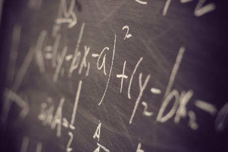 matematica: Fórmulas matemáticas escritas por tiza blanca sobre el fondo de la pizarra.