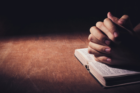 the sermon: Praying hands with bible on the wooden desk background.