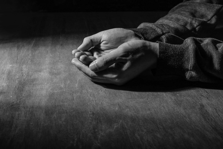 forgiven: The open praying hands on the wooden desk background. Stock Photo