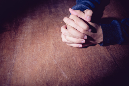 clasped hands: Praying hands of young man on a wooden desk background.