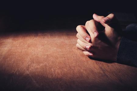 manos orando: Manos de rogación del hombre joven en un fondo de escritorio de madera. Foto de archivo