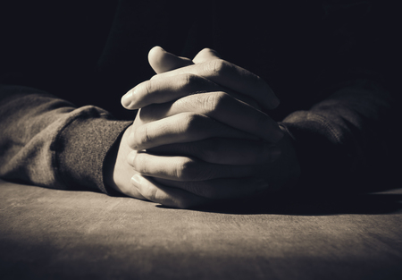 hombre orando: Manos de rogación del hombre joven en un fondo de escritorio de madera. Foto de archivo