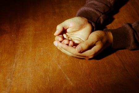 orando: Las manos orando abiertos en el fondo de escritorio de madera.