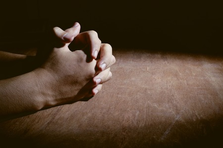 man praying: Praying hands of young man on a wooden desk background.