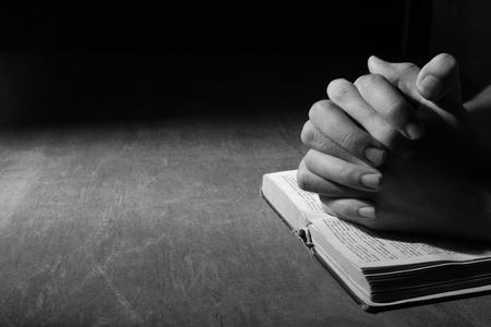 木製の机の背景に聖書を手に祈って。