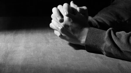 new testament: Praying hands of young man on a wooden desk background.