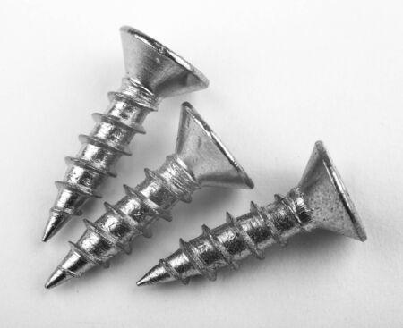 metal tips: Three screws lying on the white background. Stock Photo
