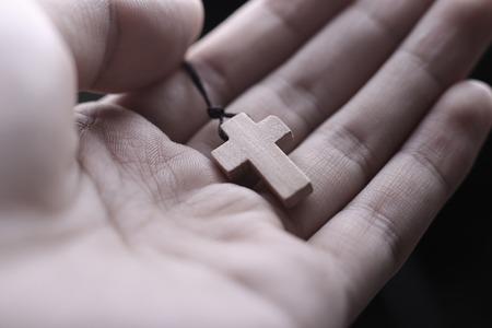 木製の十字架を持っている手を祈ってのクローズ アップ。