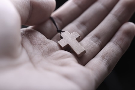 spiritual background: Closeup of praying hand holding the wooden cross.
