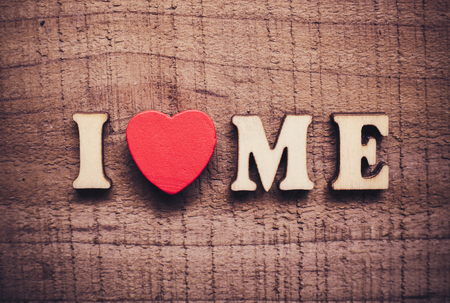 egoistic: I Love Me with rustic wooden background.