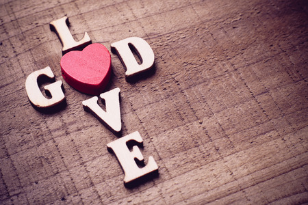 love life: God is love concept text lying on the rustic wooden background.