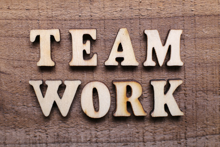 combined effort: Wooden Text Teamwork with rustic wooden background. Stock Photo