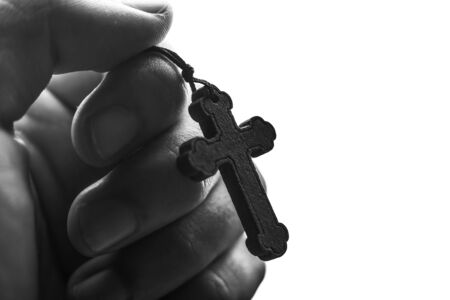 lord jesus: Closeup of praying hand holding the wooden cross.