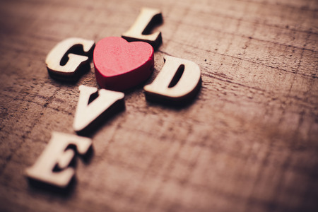 jesus word: God is love concept text lying on the rustic wooden background.