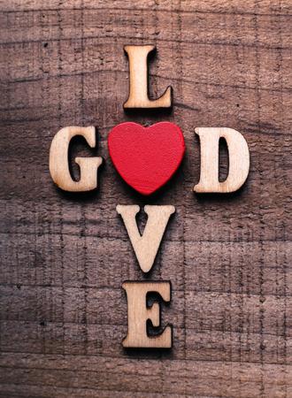 神は、素朴な木製の背景の上に横たわる愛概念テキストです。 写真素材