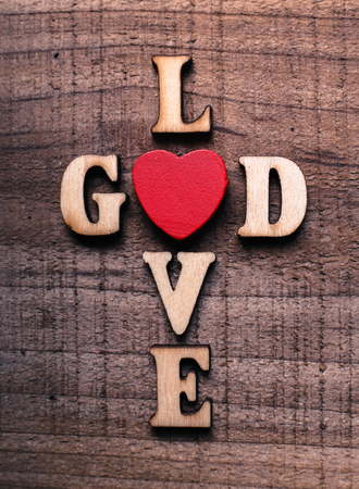 god is love: God is love concept text lying on the rustic wooden background.