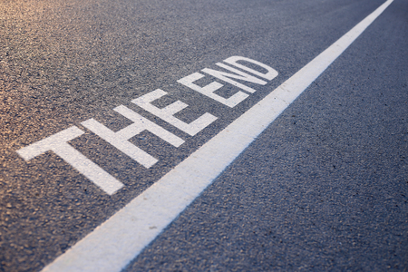 conclusive: Closeup photo of The End Word With Line on the road.
