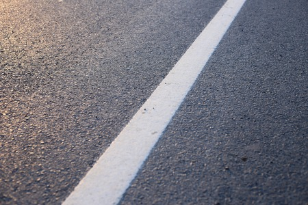 exceeded: Closeup photo of the road with white line.