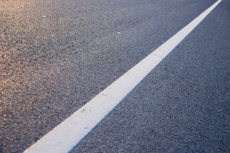 Closeup photo of the road with white line.