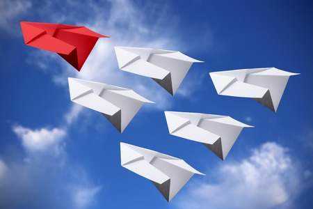 Red paper plane leading white ones in the sky. Stock Photo