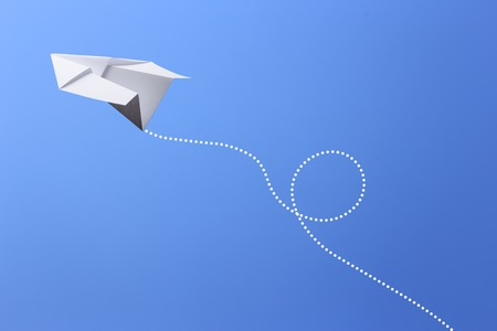Paper plane flying in the blue sky.