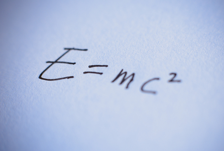 mathematical proof: The formula E=mc2 is written on the paper. Stock Photo