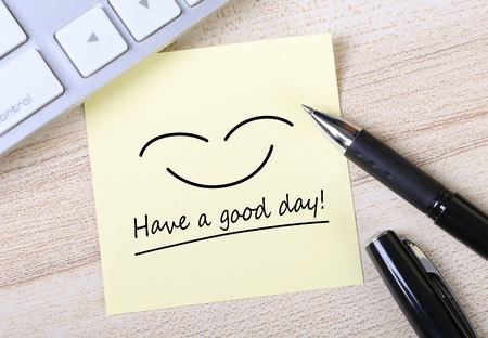 good: Top view of Have a good day sticky note pasted on the wooden desk with keyboard and pen aside. Stock Photo