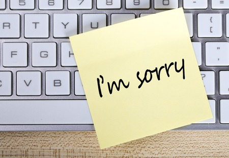 i am sorry: Top view of I am Sorry sticky note pasted on the keyboard.