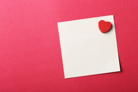 Blank Valentine sticky note with red heart pasted on red background. Stock Photo