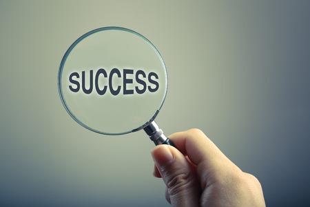 vidrio: Mano que sostiene una lupa con el texto del éxito.