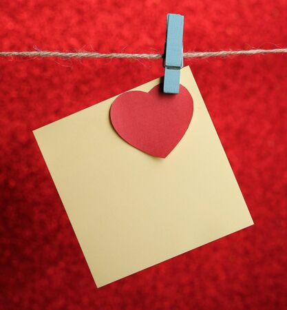 blank note: Blank sticky note with red heart hanging against red background.