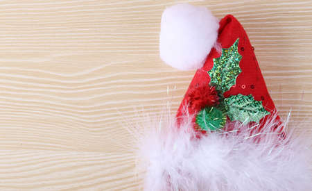 winterly: Christmas hat lying on the wooden desk background.