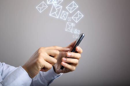 gradually: Businessman using smart phone with Email icons against gradually varied background.