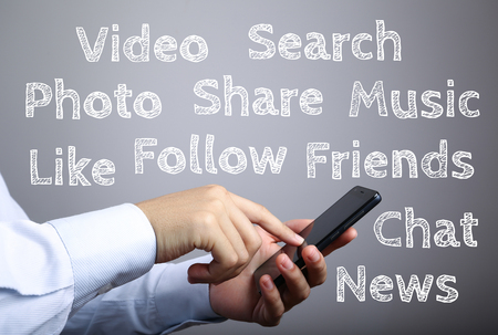 gradually: Businessman using smart phone with Social media concept words against gradually varied background.