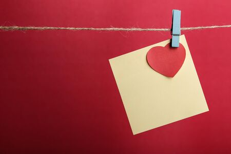 valentineday: Blank sticky note with red heart hanging against red background.