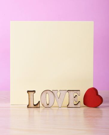 yellow tacks: Yellow sticky note book with love heart against pink background.