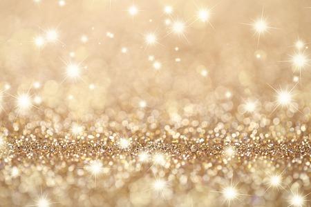 Abstract golden holidays twinkle lights on background. Standard-Bild