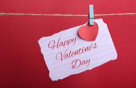 valentineday: Valentine note paper with red heart and Happy Valentines Day text hanging on line against red background.
