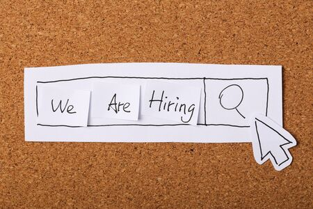 employment elementary school: We are hiring concept with wooden cork background.