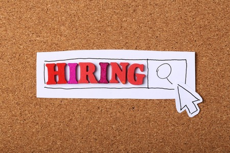 Search Hiring Online concept with wooden cork background.