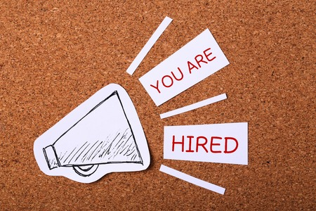 hiring: You are hired concept with wooden cork background.