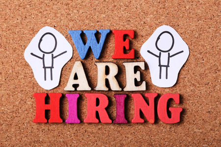 recruit help: We are hiring concept with wooden cork background.