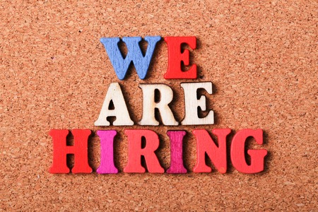 hiring: We are hiring concept with wooden cork background.