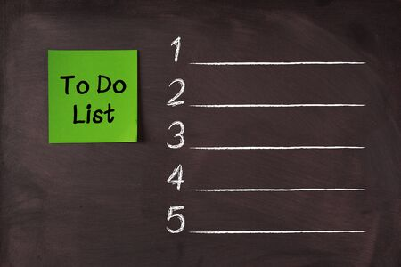 target thinking: Green To Do List sticky note pasted on blackboard.