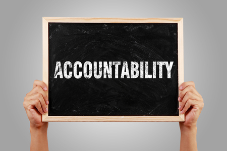 accountability: Hands holding small blackboard with text Accountability against gray background.