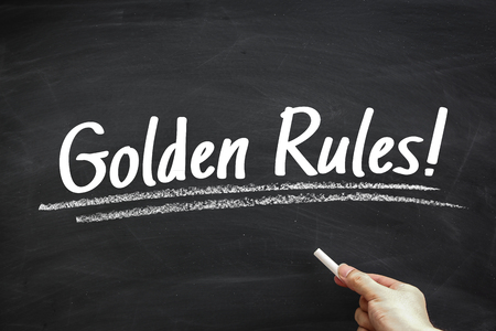 golden rule: Text Golden Rules written on the blackboard with hand holding white chalk aside.