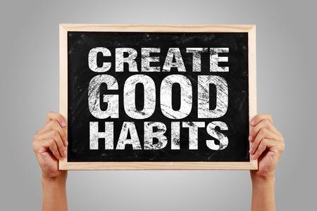 Hände halten kleine Tafel mit dem Text erstellen Gute Gewohnheiten vor grauem Hintergrund.