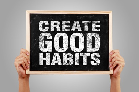 good habits: Hands holding small blackboard with text Create Good Habits against gray background.
