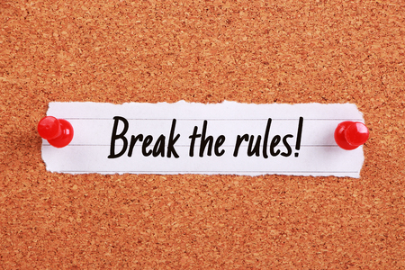 breaking the rules: Text Break The Rules written on note paper pinned on the corkboard.