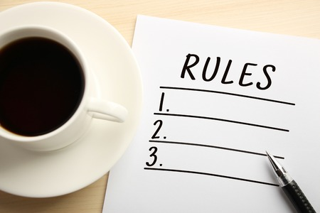 normative: Rules List written on the white paper with coffee aside.